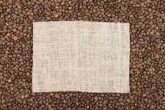 Grains of coffee in which in the center a rectangle of burlap wi stock images