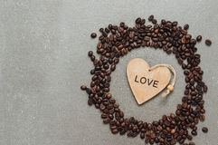 Grains of coffee and wooden heart on a gray background, top view. Stock Photos