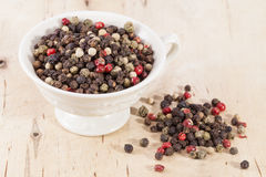 Grains of colorful pepper in the cup  on wooden plank Royalty Free Stock Photography
