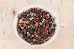 Grains of colorful pepper in the cup  on wooden plank Stock Photos