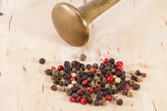Grains of colorful pepper with mortal on wooden plank Stock Photos