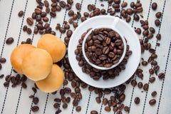 Grains de café arrosés sur le verre et le pain Photos stock