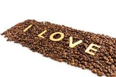 Grains de café avec des biscuits dans la forme du mot d'amour Images stock