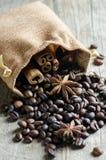 Grains de café avec l'anis et la cannelle sur le fond en bois Image libre de droits