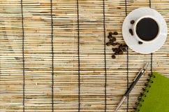 Grains de café avec la tasse blanche, le carnet vert et le stylo sur le tapis Photos libres de droits