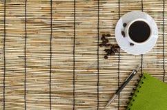Grains de café avec la tasse blanche, le carnet vert et le stylo sur le tapis Photos stock