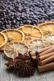 Grains de café avec les bâtons de cannelle d'agrume et l'anis d'étoile sur le fond de la toile de jute photos libres de droits