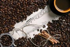 Grains de café, bâtons de cannelle et tasse de café préparé sur le fond de musique de feuille, vue de ci-dessus avec l'espace pou Image libre de droits