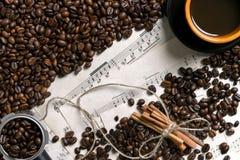 Grains de café, bâtons de cannelle et tasse de café préparé sur le fond de musique de feuille, vue de ci-dessus avec l'espace pou Photo libre de droits