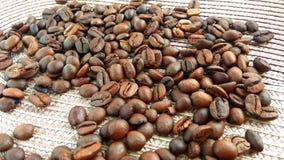 Grains de café bruns rôtis sur le fond clair de tissu images stock