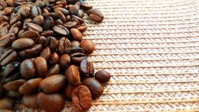 Grains de café bruns rôtis sur le fond clair de tissu de textile images stock