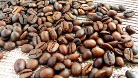 Grains de café bruns rôtis sur le fond de tissu de textile photos stock
