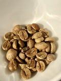 Grains de café crus d'un plat en céramique blanc photo stock