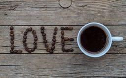 Grains de café d'AMOUR sur le fond en bois Photographie stock libre de droits
