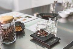 Grains de café dans des récipients spéciaux photos stock