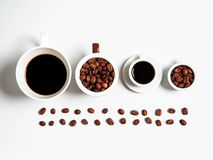 Grains de café dans des tasses d'isolement sur le blanc Photos stock