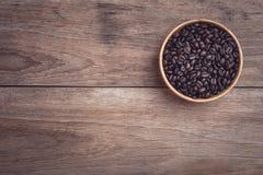 Grains de café dans la cuvette en bois sur la vue supérieure en bois de table Photo stock