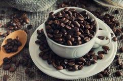 Grains de café dans la tasse blanche Photographie stock libre de droits