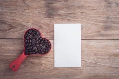 Grains de café dans la tasse en plastique de coeur rouge sur la vue supérieure en bois de table Images libres de droits