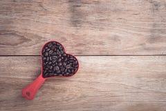 Grains de café dans la tasse en plastique de coeur rouge sur la vue supérieure en bois de table Photographie stock