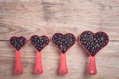 Grains de café dans la tasse en plastique de coeur rouge sur la vue supérieure en bois de table Photo libre de droits