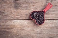 Grains de café dans la tasse en plastique de coeur rouge sur la vue supérieure en bois de table Image libre de droits