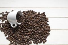 Grains de café dans la tasse sur le bois et le haricot blancs Photographie stock