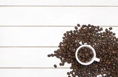 Grains de café dans la tasse sur le bois et le haricot blancs Photos stock