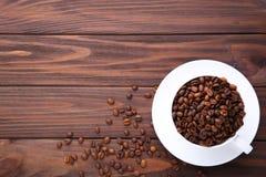 Grains de café dans la tasse sur le fond en bois brun photographie stock libre de droits