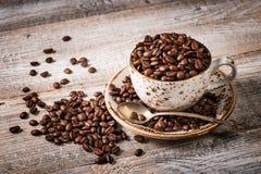 Grains de café dans la tasse sur la table en bois images stock