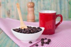 Grains de café dans le bolw avec la tasse Images stock