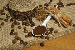 Grains de café dans le pot, cafè moulu dans une cuillère, cannelle Image stock