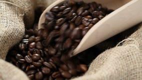 Grains de café dans le sac à toile de jute avec le scoop en bois banque de vidéos
