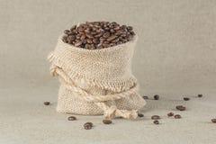 Grains de café dans le sac de toile de jute Images stock