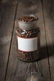 Grains de café dans un pot en verre placé sur la table en bois Photos libres de droits