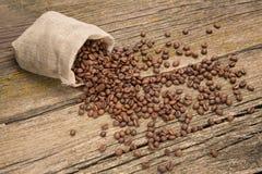 Grains de café dans un sac sur des conseils Images libres de droits