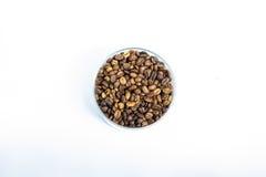 Grains de café dans un verre sur un fond blanc Photo stock