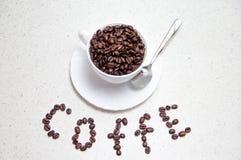 Grains de café dans une cuvette blanche Grains de café dispersés photos stock