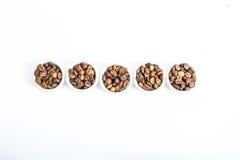 Grains de café dans une cuvette sur un fond blanc Photographie stock libre de droits