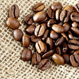 Grains de café de Brown sur un sac de jute. Photos stock