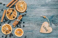 Grains de café, de cannelle et d'orange sèche sur un fond en bois bleu Un coeur en bois avec un mot de l'amour Image libre de droits