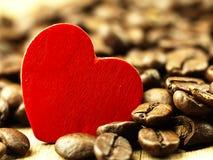 Grains de café de coeur et en gros plan sur en bois, table de chêne Photo libre de droits