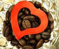 Grains de café de coeur et en gros plan sur le verre Image libre de droits