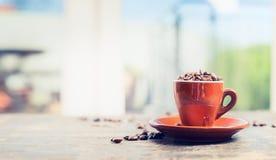 Grains de café de tasse d'expresso pleins sur la table de jardin ou de terrasse au-dessus du fond de nature Photo stock