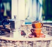 Grains de café de tasses de café pleins et de pot sur la table de jardin ou de terrasse au-dessus du fond de nature Images stock