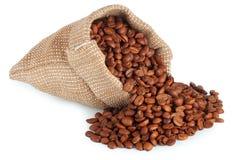 Grains de café dispersés dans l'isolat de sac de toile de jute Photographie stock