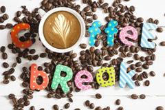 Grains de café dispersés sur la table blanche avec le message de pause-café photo stock