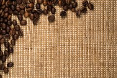Grains de café dispersés sur la toile de jute Photos libres de droits