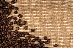 Grains de café dispersés sur la toile de jute Photo libre de droits