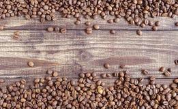 Grains de café dispersés sur un fond en bois images libres de droits